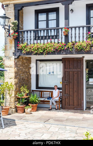 Santillana, Spain - 8th July 2018: Woman sat on bench outside  Hotel Colonial de Santillana. This is one of several hotels in the town. - Stock Image