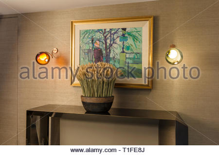 Potted plant on table under painting - Stock Image