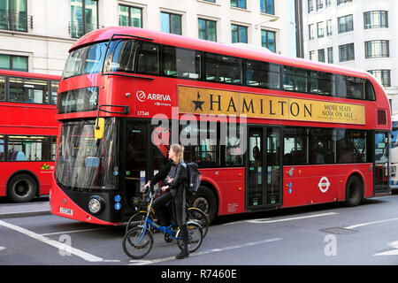 Red double-decker bus with advert on the side for the American West End theatre play HAMILTON and cyclists waiting on bikes in London UK  KATHY DEWITT - Stock Image