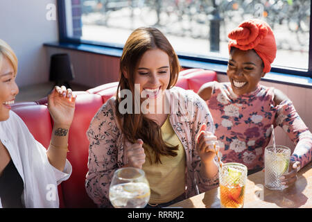 Happy, excited young women drinking cocktails in restaurant - Stock Image