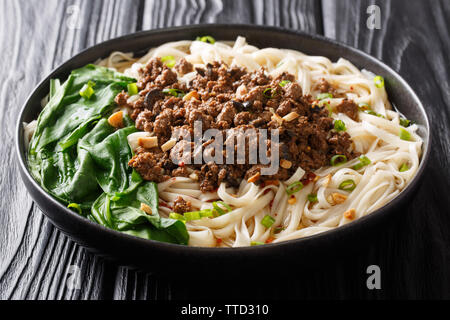 Spicy Dan Dan Noodles with minced meat and herbs served with hot sauce in a plate on the table. horizontal - Stock Image