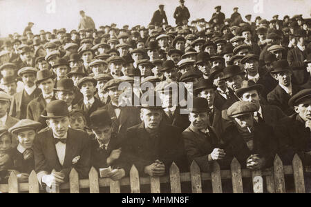 An all-male crowd of smartly dressed spectators observe proceedings from behind a picket fence, perhaps at a sporting event in the north east of England.     Date: c.1910s - Stock Image