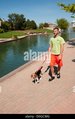 USA, Indiana, Indianapolis, canal in downtown area, man walking dog - Stock Image
