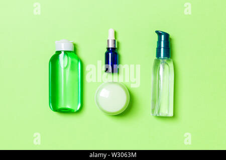 Cosmetics SPA branding mock-up, top view with copy space. set of tubes and jars of cream flat lay on green background. - Stock Image