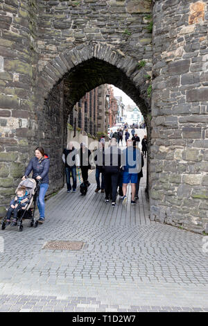 Tourists and locals passing through the old wall arch on Conwy Quay in North Wales which leads from the quay at Lower Gate Street to the High Street - Stock Image