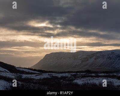The glow of late afternoon sun through the clouds over central Iceland - Stock Image