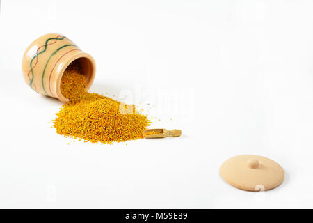 Bee pollen poured out from a small glazed clay pot. Next to the pile of pollen lies one little wooden scoop. In - Stock Image