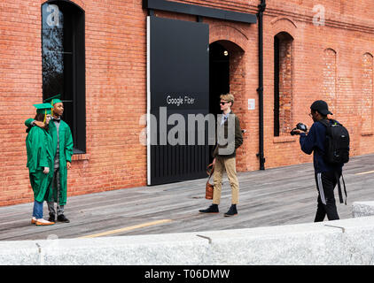 CHARLOTTE, NC, USA-3/16/19: Young man and woman have their pictures taken, wearing graduation gowns, in front of Gpogle Fiber building. - Stock Image