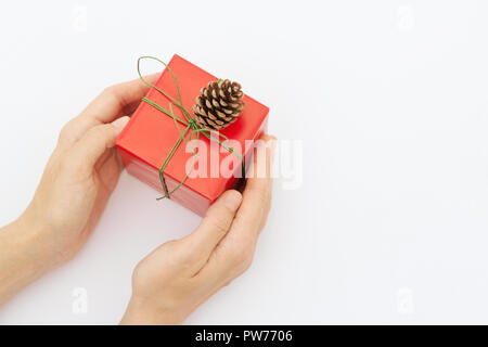 Young caucasian woman holds in hands gift box wrapped in red paper tied with green ribbon. White background pastel colors. Christmas New Years present - Stock Image