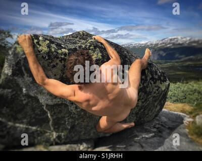 The naked climber, bouldering on a big rock in Hardangervidda National Park, Norway. - Stock Image