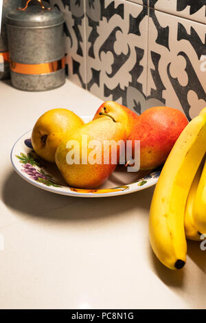 Four Bartlett pears, Pyrus communis, in a plate decorated with fruit. Bananas on the side. - Stock Image