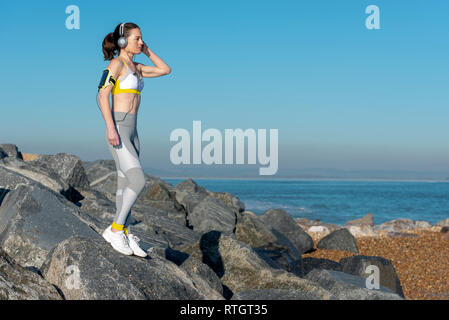 woman wearing sportswear standing on rocks looking out to sea listening to music on her smartphone, relaxing after exercise - Stock Image