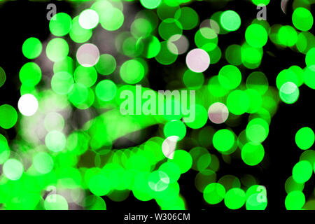 Unfocused abstract colourful bokeh black background. defocused and blurred many round green light. - Stock Image