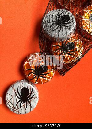 Hallowe'en themed foil wrapped spider chocolates in black net bag on an orange background with copy space - Stock Image