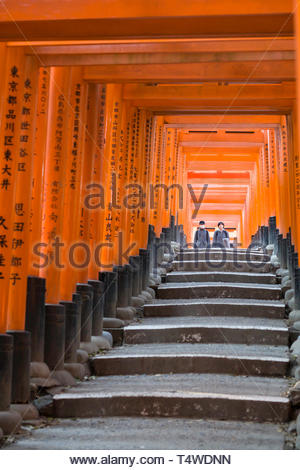 Man and woman walking beneath the Senbon Torii painted in a vermilion red-orange color that is associated with the soul of Inari Okami and blessings f - Stock Image