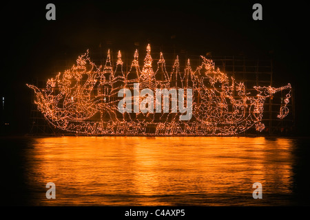 Thailand, Nakhon Phanom, That Phanom.  A Fire Boat drifts on the Mekong River during the Illuminated Boat Procession. - Stock Image