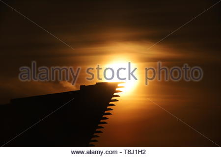Dundee, UK. 14th May, 2019. The dramatic silhouette of the V&A Design Museum at sunrise in Dundee, a bright start to a warm sunny day in Tayside. Credit: Stephen Finn/Alamy Live News - Stock Image