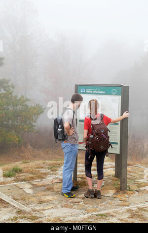 Hikers looking at trail map, Pilot Mountain, North Carolina. - Stock Image