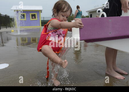 A toddler washes her feet in water at a splash pad during the summer. - Stock Image