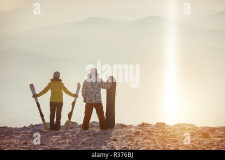 Skier and snowboarer stands on mountain top at ski resort - Stock Image