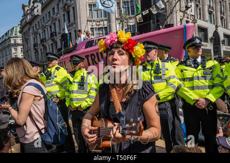 London, UK. 19th April 2019. A woman plays and sings in the crowd at Extinction Rebellion's Sea of Protest after police surrounded the yacht at Oxford Circus. Police began a slow process of persuading protesters to leave by threatening them with arrest and cutting off those who were locked on around the bottom of the yacht. There were a number of arrests of protesters who refused to leave. A few tried to get the large crowd to protect the yacht, but XR organisers persuaded them not to physically oppose the police action. Peter Marshall/Alamy Live News - Stock Image