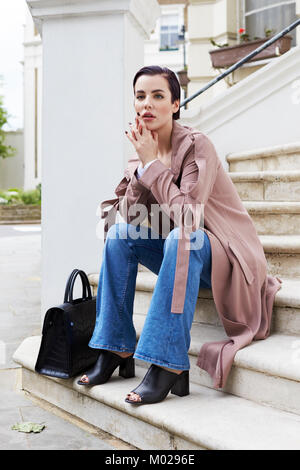 Woman in coat and jeans sitting on steps outside a house - Stock Image