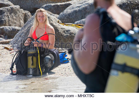 Woman in wetsuit checking scuba equipment on beach smiling at dive partner - Stock Image