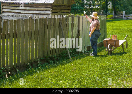 GOLDEN POND, KY, USA-30 JUNE 18: An interpreter and worker whitewashing a fence at  The Homeplace, an 1850s working farm. - Stock Image