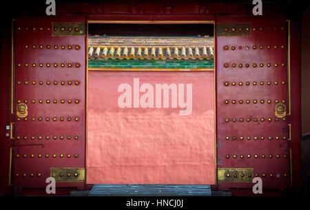 Ancient red wooden doors at the Forbidden City, Beijing - Stock Image