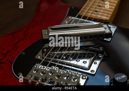 Harrmonica on an old electric guitar. Blues, rock music, - Stock Image
