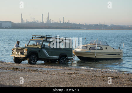 Two men launching a small boat down a ramp into the Solent using a four wheel drive vehicle, Hampshire, UK - Stock Image