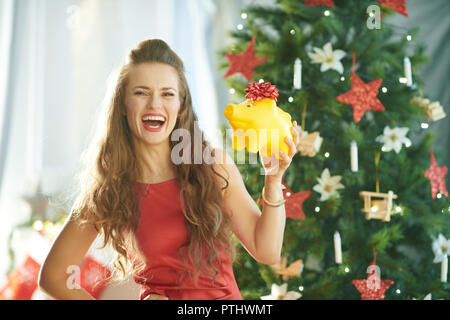 Portrait of smiling young woman in red dress with yellow piggy bank near Christmas tree - Stock Image