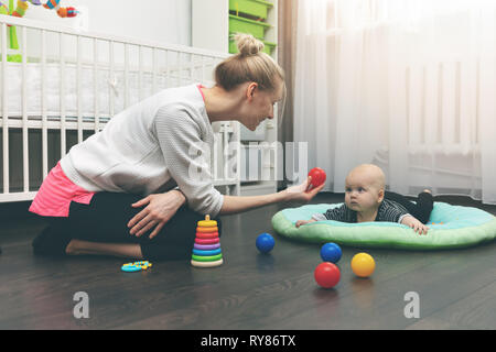 babysitting - nanny playing with little baby on the floor at home - Stock Image