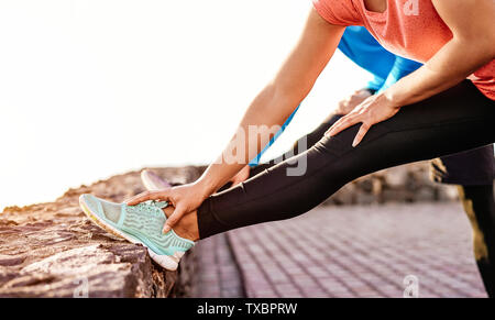 Fit couple stretching and training legs outdoor - Sporty young people doing workout session exercises next the beach - Stock Image