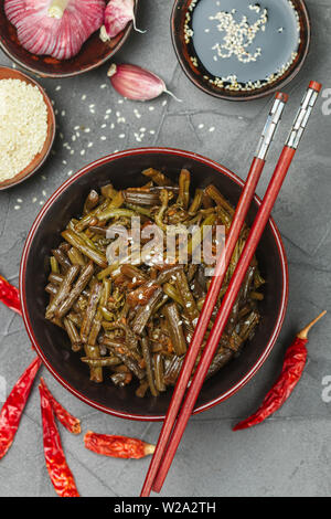 Spicy bracken  fern salad with onion, garlic, chili pepper, soy sauce, sesame seeds and spices. Oriental and Asian dishes. Chinese, Korean, Japanese c - Stock Image