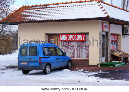 Blue delivery car parked in front of a small grocery shop in the winter season in Poznan, Poland - Stock Image