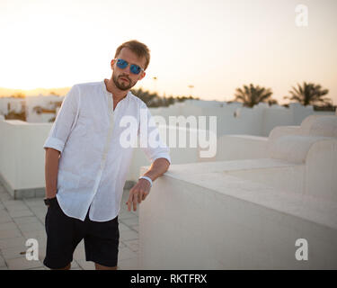 Young man stands on the roof of building in white shirt and sunglasses at sunset. Copy space. - Stock Image