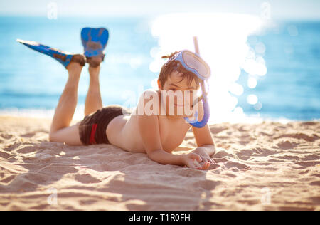 Child lying on the beach with swimming mask - Stock Image