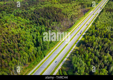 Straight highway through deep forest aerial view. Bright summer image at sunny day - Stock Image