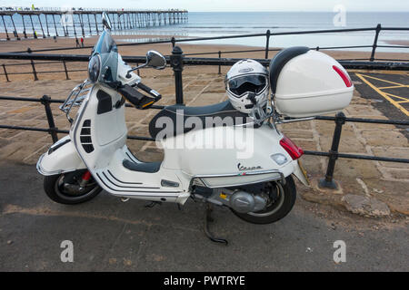 A smart well equipped White Vespa motor scooter at Saltburn Beach - Stock Image