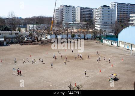 Children at play on dirt field school yard - Stock Image