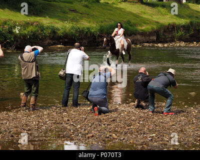 female traveller riding horse in the River Eden, Appleby-in Westmorland as organised photo opportunity for assembled photographers at the crowded annual Appleby Horsefair,  UK, 8 June, 2018. photographers swarm around female rider in River Eden Credit: Steve Holroyd/Alamy Live News - Stock Image