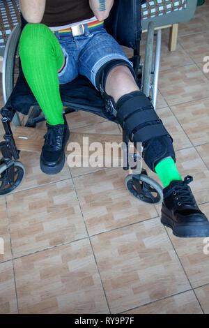 Woman in Leg Brace in Wheel Chair - Stock Image
