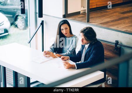 Businessman discussing with colleague at desk in office - Stock Image