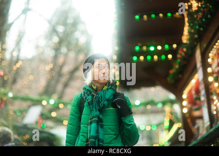 Mature woman shopping at Weihnachtsmarkt, Freiburg, Baden-Wurttemberg, Germany - Stock Image
