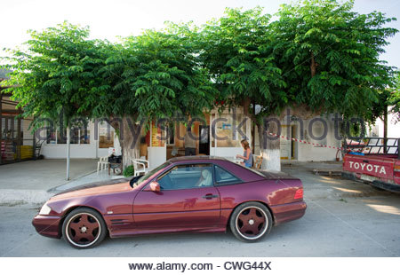 Greek cafe with expensive car parked outside coffeeshop - Stock Image