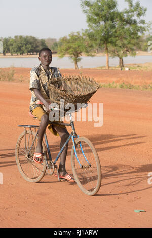 Samba village, Yako Province, Burkina Faso: A young fisherman on his way with his fishing baket to catch fish in the lake on one of the days when fishing is allowed. - Stock Image