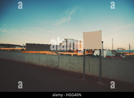Mock up of empty white billboard near seaside and industrial zone, low concrete fence behind, sunset with clear - Stock Image