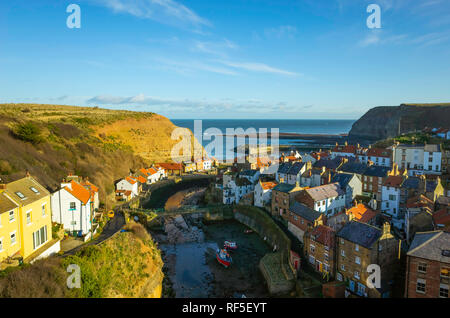 View looking seawards over the harbour of the North Yorkshire Village of Staithes with Cowbar on the North side of Roxby Beck - Stock Image
