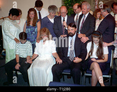 several people praying for a family going through rough times - Stock Image